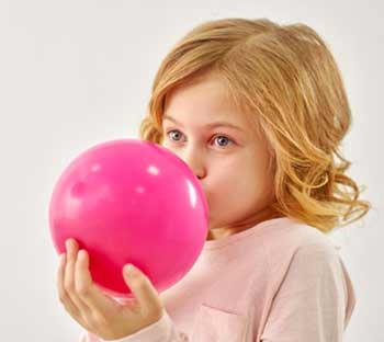 Julie souffle une balloune pour l'anniversaire de sa petite sœur.