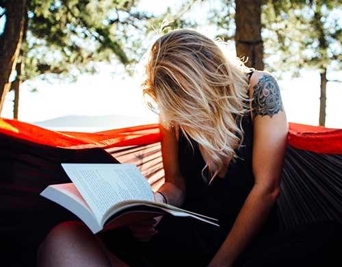 Une femme qui lit une brique, équivalent québécois du pavé français.