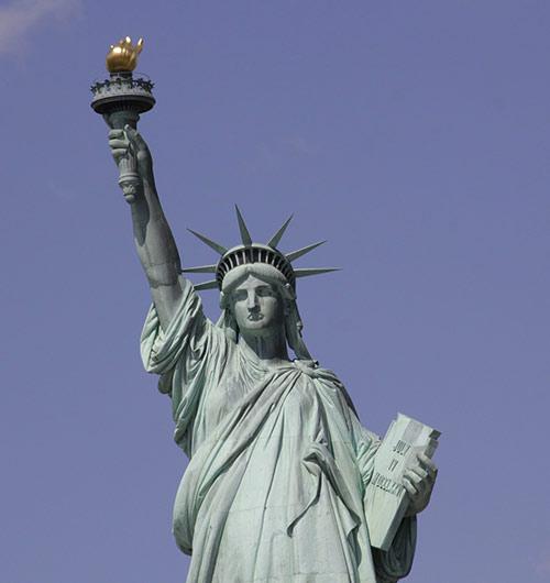Image de la statue de la liberté portant fièrement le flambeau de la liberté. Certains donnent le surnom de « la grosse torche » à la statue de la Liberté pour jouer sur les deux sens du mot torche.