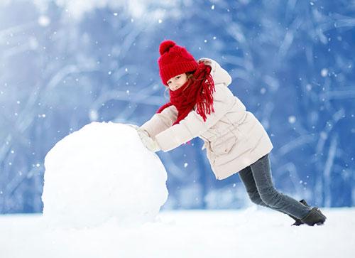 Une petite fille construit un bonhomme d eneige. La neige est idéale, de la vraie neige à bonhomme. En québécois, la neige à bonhomme est de la neige mouillée.