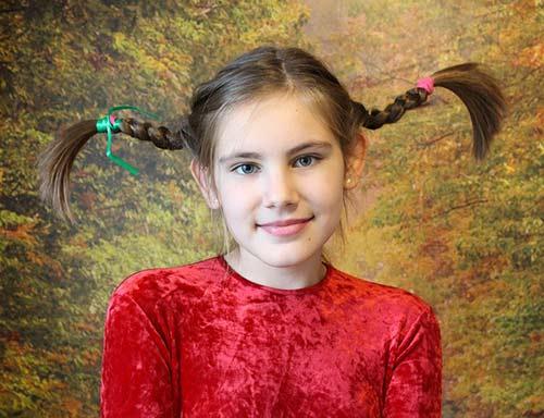 Une jeune fille a de longues tresses, comme celles de Fifi Brindacier. Elle a une drôle de peignure. Le mot peignure signifie coiffure dans la langue québécoise.