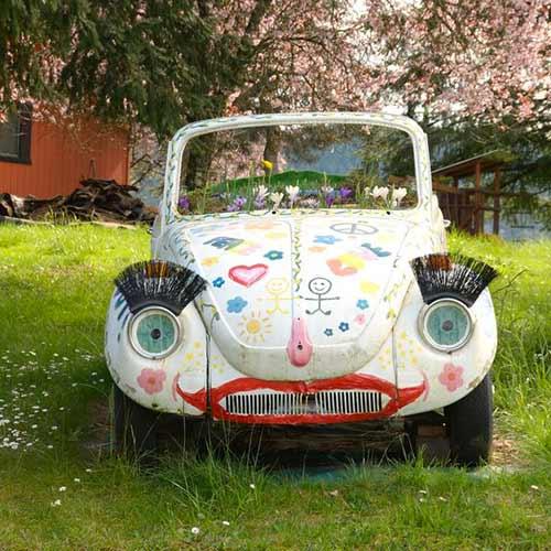 Une vieille volkswagen couverte de dessins d'enfant semble à l'abandon dans une cour. Cette voiture est une minoune. Un des sens québécois du mot minoune est celui de voiture en mauvais état.