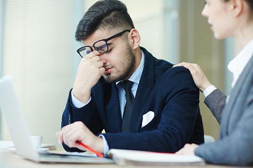 Un homme déprimé se fait consoler par sa collègue de travail. «Jules a donc la falle basse», expression québécoise synonyme d'être déprimé.