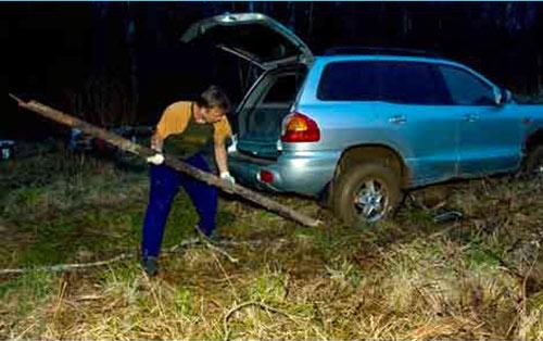 Un homme tente de déprendre sa voiture embourbée à l'aide d'un tronc d'arbre brisé. Il gosse, verbe québécois qui signifie tenter de grands efforts maladroit pour accomplir une tâche.