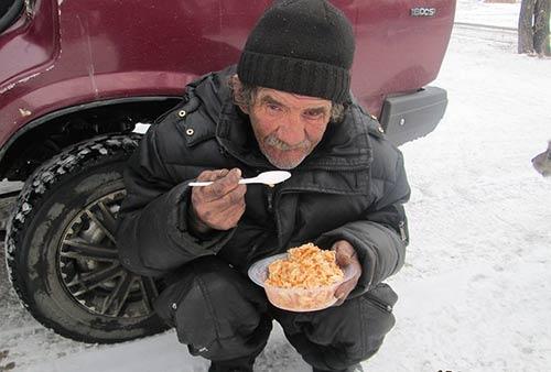 Un robineux (sans-abri) mange accroupi dans la neige.
