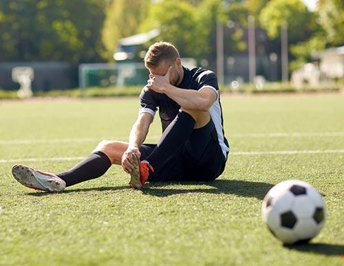 Un jouer de soccer est assis au sol, en douleur. Il a reçu un coup dans le schnolles, un mot québécois qui signifie les testicules.