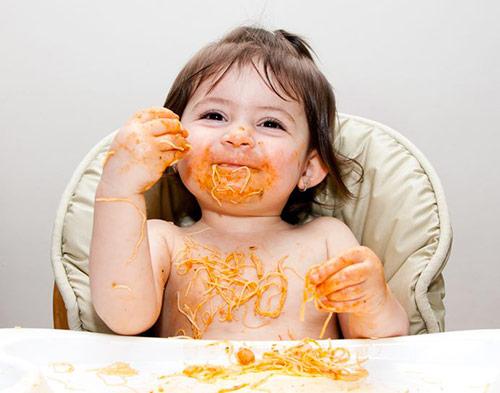 Une petite fille mange avec plaisir du spaghetti. Elle en sur tout le visage, les mains et le torse. Elle dit : c'est bon en tabarnouche. Un juron ou une exclamation inoffensive du Québec.
