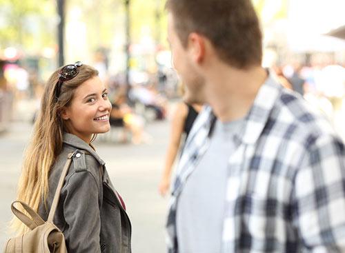 Une jeune fille sourit à un homme sur la rue. Elle a un œil sur lui, une expression qui au Québec signifie désirer quelqu,un alors qu'en France, cette expression veut dire surveiller quelqu'un.