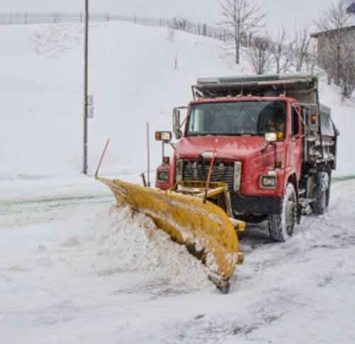 Un chasse-neige déblaie une rue de campagne enneigée. Au Québec, on dit aussi charrue comme synonyme de chasse-neige.
