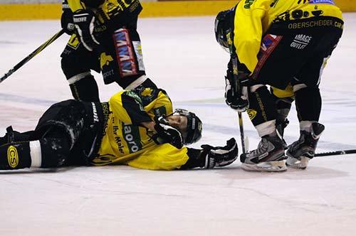 Un joueur d ehockey est étendu sur la glace après avoir reçu un coup dans les gosses. Gosses est un mot québécois synonyme de testicule.