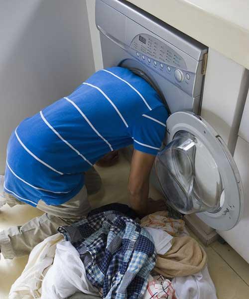 Un homme a la tête dans une laveuse (lave-linge en France) à la recherche d'un morceau de vêtement perdu.