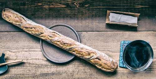 Sur un table de bois, une baguette et un café fumant. Au Québec, nous disons pain français plutôt que baguette.
