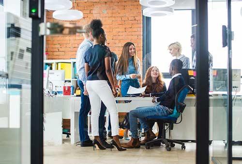 Un groupe d'employés placotent autour d'un bureau. Au Québec, le verbe placoter signifie bavarder.