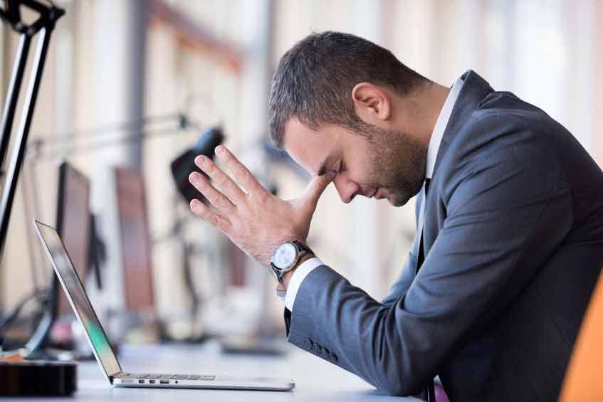 Un homme devant son ordinateur tente de se calmer. Il en a plein son casque de son travail. une expression québécoise qui signifie ne plus être capable de supporter quelque chose, en avoir assez.