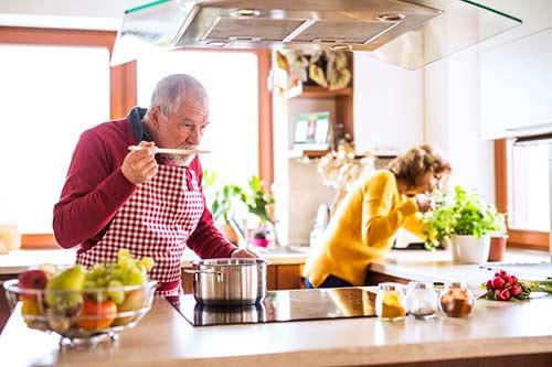 Un couple âgé font la cuisine. L'homme se tient devant le poêle, nom donné à la cuisinière par ce nombreux Québécois.