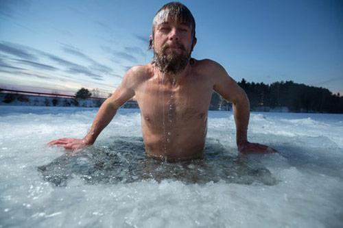 Un homme plonge en maillot de bain dans l'eau d'un lac en partie couvert de glace. Il dit : c'est frette en tabarouette! Un juron québécois.