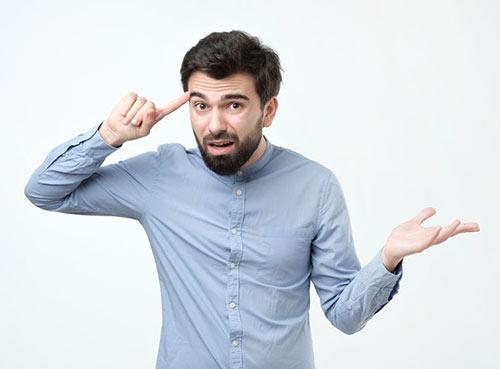 Un homme exaspéré un doigt sur la tête, exaspéré par la stupidité de son interlocuteur, lui demande : à cause tu fais simple de même.