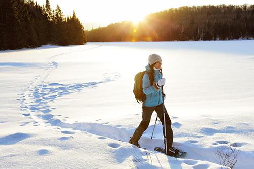 Dix expressions québécoises d'hivers. Une jeune femme marche avec des raquettes dans sur un lac gelé couvert de neige.