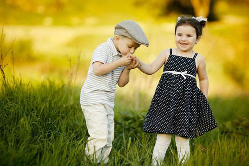 L'expression chanter la pomme signifie faire la cour à quelqu'un, tenter de séduire. Un petit garçon de quatre ans fait un baise-main à une petite fille, qui lui sourit timidement.