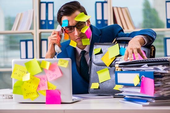 Un homme est débordé : des post0it recouvre son ordinateur, il tien sa valise pendant qu'il parle au téléphone tout en lisant une pile de dossier.
