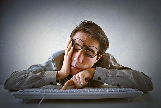 L'expression dormir sur la corde à linge : Un homme avachi à son clavier tente de rester éveillé à son travail.