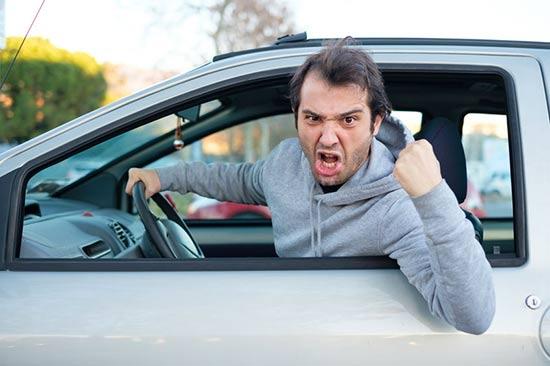 Un conducteur enragé hurle sa colère à un autre conducteur : Il lui crie : «Ostie de malade, tu sais pas chauffer».