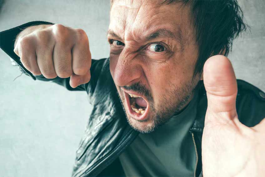 Un homme enragé mon tre soin poing fermé, prêt à se battre. Au Québec, on dit qu'il est en câlice.