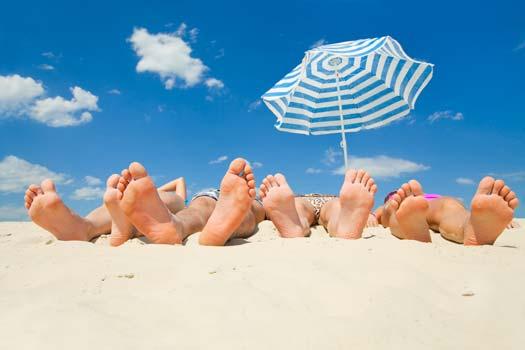 Sur une plage, une famille se fait dorer la couenne au soleil.