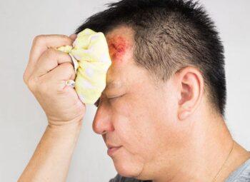 Un homme tient un sac de glace sur une blessure à la tête : il s'est cogné la bolle.
