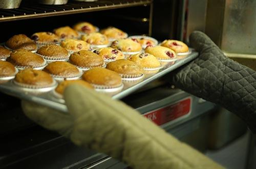 À l'aide de ses mitaines pour le four, une personne sort un plat de muffin du four brûlant.