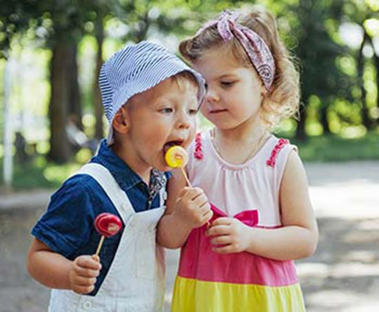 deux jeunes enfants se partagent leur suçon. Ce sont de vrais bibittes à sucre.